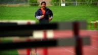 slow motion dolly shot Hispanic man running with prosthetic leg toward camera on track