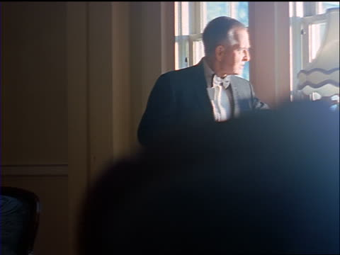 slow motion dolly shot senior man wearing tuxedo walking to window of room fixing cuff links + picking up picture