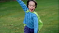 Slow motion edium shot focus boy playing superhero in park with cape tied around neck/ defocus as boy gets closer/ Maine