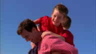 Slow motion father holding and playing w/twin boys on blanket at beach