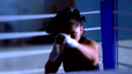 slow motion MS female boxer facing camera shadow boxing with taped hands in ring