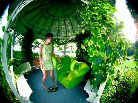 slow motion FISHEYE crane shot PORTRAIT Asian woman sits in green chair in gazebo with ivy + small bouncing lights
