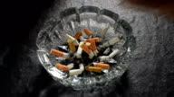 Slow motion footage of hand pushing lit cigarette butt in an ashtray