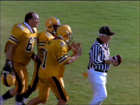 slow motion football players arguing with referee