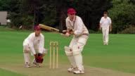 slow motion PAN from cricket batsman hitting ball to fielder running after ball / Hertfordshire, England