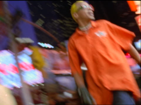 slow motion PAN Gen X man with yellow hair skating past camera on street in Times Square at night