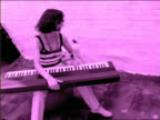 B/W PINK slow motion Gen X woman playing keyboard + singing outdoors while dog looks on