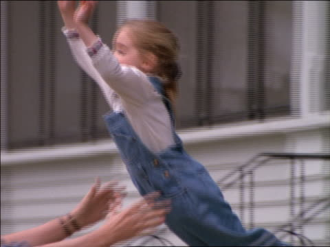 slow motion girl in overalls jumping into arms of father outdoors
