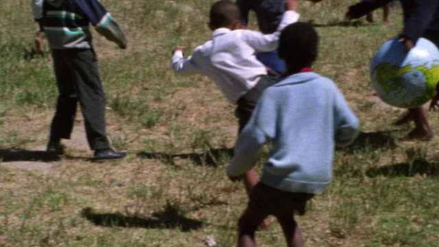 Slow motion group of barefooted Black children play soccer with inflatable globe outdoors / South Africa
