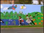 slow motion PAN group of Black children running past children's mural on sidewalk