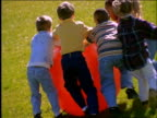 slow motion group of children playing with large rubber ball / Connecticut
