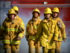 slow motion MS group of firefighters walking towards camera in protective equipment with truck in background
