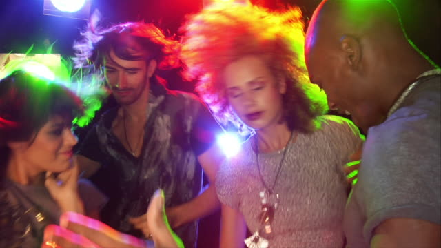 Slow motion handheld young people dancing amid colored lights
