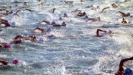 slow motion high angle crowd of swimmers racing in ocean / Iron Man competition, Hawaii