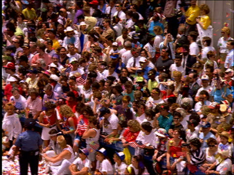 slow motion high angle PAN of crowd watching ticker tape parade / Operation Welcome Home / NYC