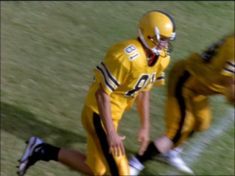 slow motion high angle football player running + catching ball / gets tackled