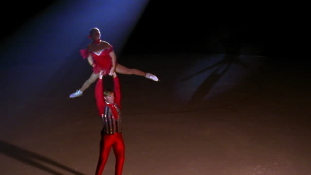 slow motion high angle male figure skater turning while holding female skater above head in pose in spotlight