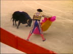 slow motion high angle matador stepping aside as bull charges through pink + yellow cape