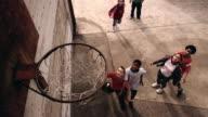 Slow motion high angle medium shot girl shooting basketball / boys battling for rebound