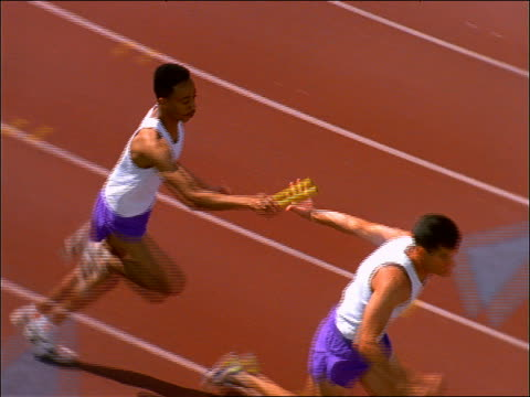 slow motion high angle of 2 men passing baton in relay race