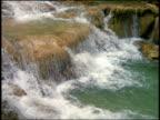 slow motion high angle waterfall going over rocks into pool / Jamaica