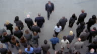 Slow motion high angle wide shot overhead view of crowd of businesspeople walking / man walking towards crowd