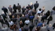 Slow motion high angle wide shot overhead view of man fighting his way through crowd of businesspeople
