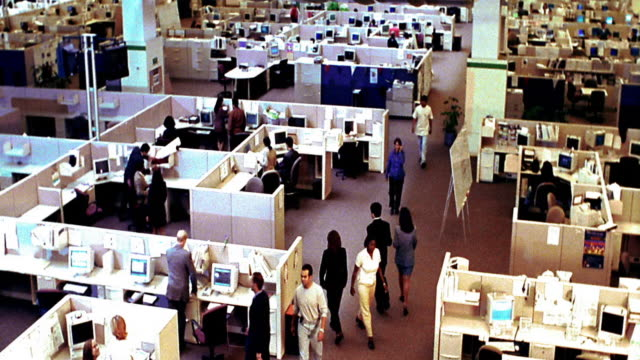 slow motion high angle wide shot time lapse office workers working + walking around in large open office with cubicles