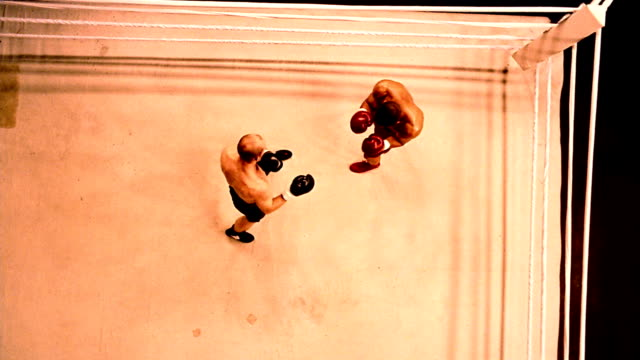 Slow motion high angle wide shot two boxers beginning to fight in ring