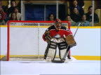 slow motion ice hockey goalie in game keeps puck from goal, then misses / fans in background