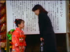 slow motion Japanese businesswoman + young girl in kimono bowing to each other outdoors / Japan