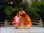 slow motion Japanese mother + 2 daughters in kimonos bowing to camera outdoors / Japan