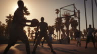 Slow motion lens flare shot of basketball game near Venice Beach, California