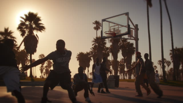 Slow motion lens flare shot of basketball players playing near Venice Beach, California