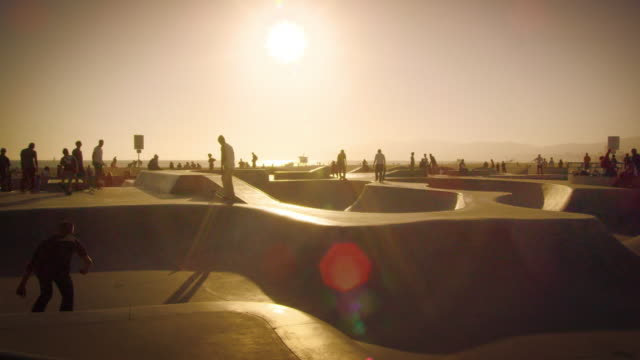 Slow motion lens flare shot of people at the skate park near Venice Beach, California