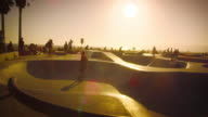 Slow motion lens flare shot of skateboarders on ramp near Venice Beach, California