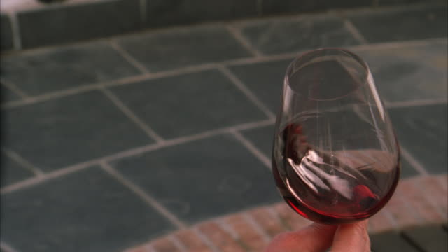 Slow motion locked off shot of a hand swirling red wine in a glass