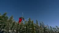 Slow motion long shot freestyle skier doing back flip through air / landing