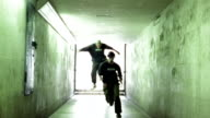 Slow motion long shot three freerunners running down hallway and jumping + flipping off walls