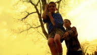 YELLOW slow motion low angle boy pushing other boy on rope tree swing / Montana