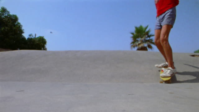 1976 slow motion low angle close up legs and feet of teenage boy riding skatebaord down hill toward + past CAM