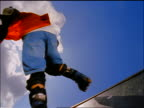 slow motion low angle close up man on inline skates performing spinning stunt on half-pipe ramp