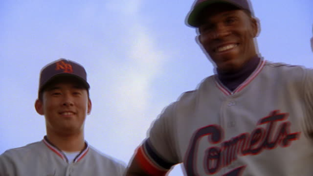 slow motion low angle close up PAN PORTRAIT three smiling Black, Asian,+ Causcasian baseball players standing outdoors