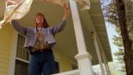 slow motion low angle MS crane shot toward woman shaking tablecloth on porch / Montana