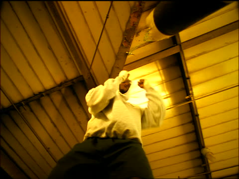 SEPIA slow motion low angle dolly shot Black male athlete punching heavy bag hanging from ceiling beam