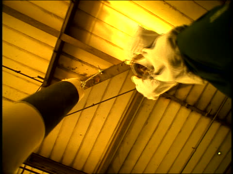 FLASH FRAMES SEPIA slow motion low angle dolly shot Black male athlete punching heavy bag hanging from ceiling beam