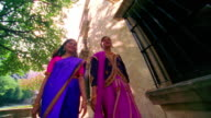 slow motion low angle dolly shot tracking shot two young Indian women in saris walking on sidewalk next to apartment building