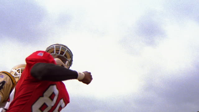 slow motion low angle MS PAN football player catching ball as opposing player tries to grab him