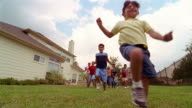 Slow motion low angle long shot children running across lawn in backyard and jumping over CAM