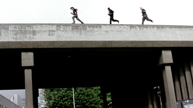 Slow motion low angle long shot three freerunners running across bridge as cars pass underneath